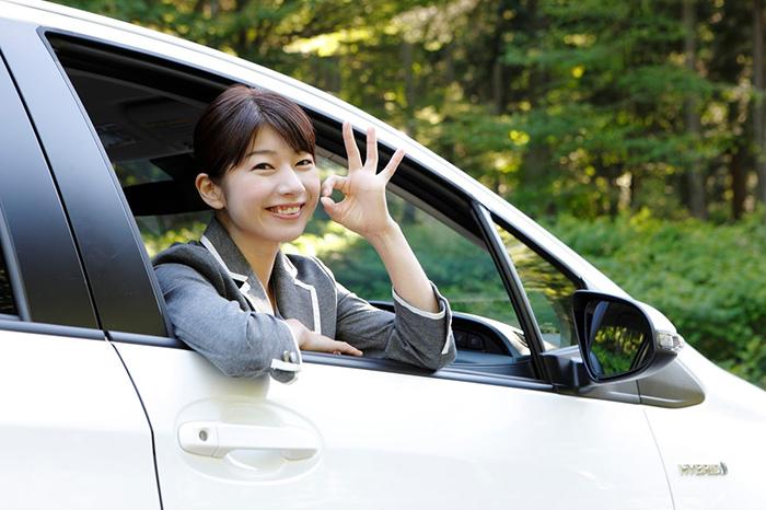 運転席からオーケーサインをとる女性