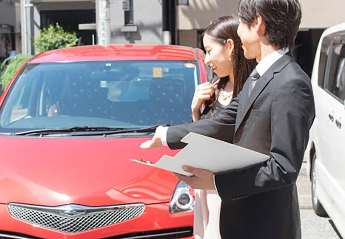 車について話し合うスタッフと女性